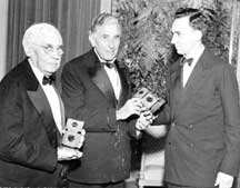 Huntington Hartford presenting commemorative clocks to George L. and John Hartford at 1947 testimonial dinner